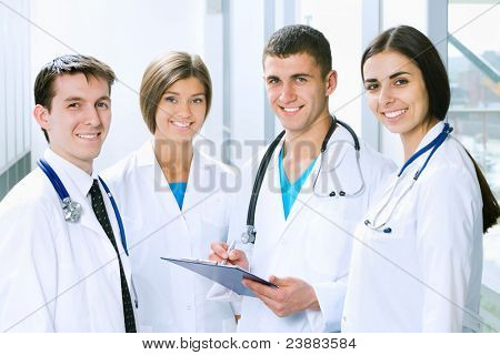 Young doctors are standing inside the hospital and looking at camera