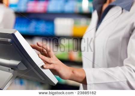 Female pharmacist standing at the cashier in pharmacy, only torso to be seen