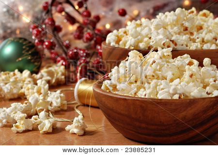 Christmas still life of popcorn being strung together to create garland for the tree.  Decorations and berries in soft focus in background.  Closeup with shallow dof.