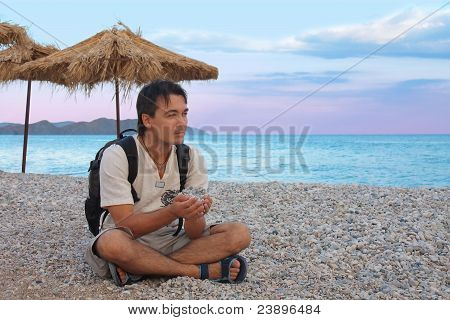 Young Man Sitting On Pebbled Beach With Stones In Hands And Relaxing