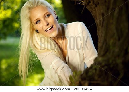 Happy Female Hiding Behind A Tree