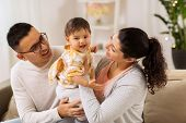 family, parenthood and people concept - happy mother, father with baby daughter at home poster