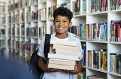 Middle eastern boy holding a stack of books against multi colored bookshelf in library. Portrait of poster