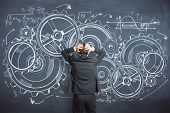 Back View Of Young Pensive Businessman Standing On Chalkboard Background With Cogwheel Sketch. Risk  poster