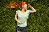 Young Relaxing Redhead Girl Lying On The Grass. Woman Relaxation Outdoor poster