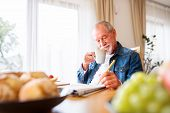 Senior Man Eating Breakfast And Doing Crosswords At Home. An Old Man Sitting At The Table, Relaxing. poster