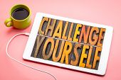 challenge yourself - word abstract in vintage letterpress printing blocks on a digital tbalet with a poster