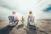 Couple On A Deck Chair Relaxing On The Beach. Happy Couple Enjoy On The Beach During Summer Vacation poster