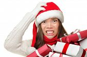 Christmas stress - busy woman wearing santa hat stressing for christmas shopping holding may christm