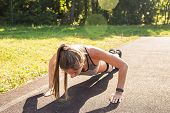 Fitness Woman Doing Push-ups During Outdoor Cross Training Workout. Beautiful Young And Fit Fitness  poster