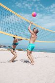 Beach Volleyball Concept. Couple Have Fun Playing Volleyball. Young Sporty Active Couple Beat Off Vo poster