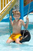 picture of tire swing  - 	Boy on tire swing in pool - JPG