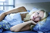 stock photo of laying-in-bed  - Worried young woman laying in bed sleepless at night - JPG