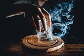 Barman Prepares Cocktail With Smoke, Raises A Glass, Pours Alcohol. Dark Background. poster