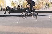 Bmx Bike Racing In A Park Skate. Bmx Rider Makes A Trick On The Handrail. The Videographer Removes A poster