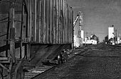 pic of railcar  - Quiet scene of a rural town with an old rusty railcar covered with graffiti waiting on a rail siding - JPG