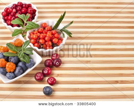 Fresh sweet berries in a wooden striped surface board texture background