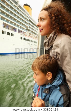 Mother and son watch on huge cruiser from which they float away on boat
