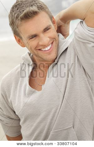 Outdoor natural portrait of a great looking young male model with big toothy smile