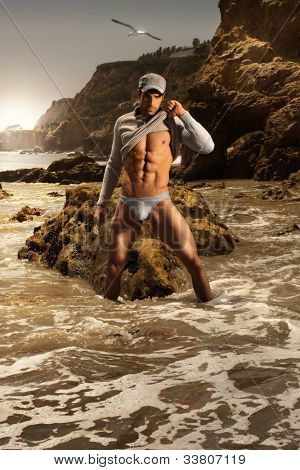 High fashion portrait of sexy male model in stunning beach setting