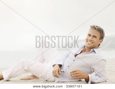 Bright outdoor fashion lifestyle portrait of a great looking young male model with nice happy smile lying down in classic casual clothing