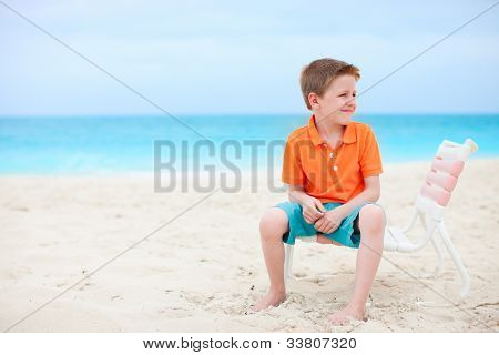 Happy boy sitting on chair at tropical beach