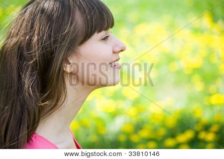Beautiful young woman enjoying the Sun on the meadow with   yellow flowers on a warm summer day