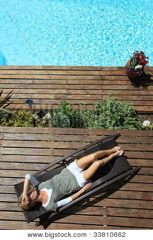 Woman relaxing in deck chair by swimming pool