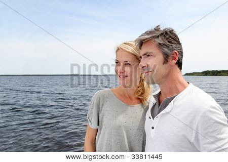 Couple embracing each other on a bridge by a lake
