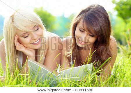 Two young beautiful smiling women reading book, sitting on grass at summer green park.