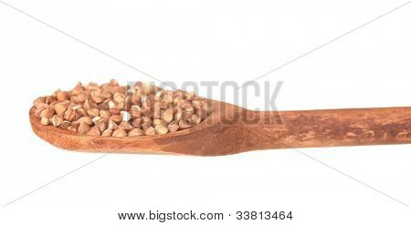 Wooden spoon with raw buckwheat isolated on white