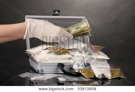 Cocaine and marijuana in a suitcase wiht hand isolated on white