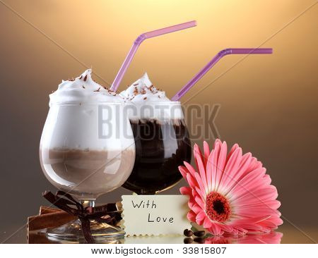 glasses of coffee cocktail and gerbera flower on brown background