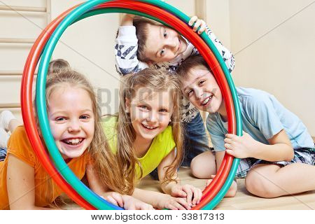 Laughing children holding hula hoops in a school gym