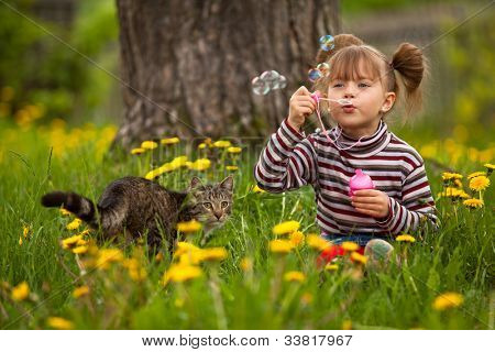 Portrait of funny lovely little girl and a cat, blowing soap bubbles
