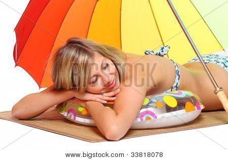 Mujer joven en traje de baño descansar bajo una sombrilla de playa.