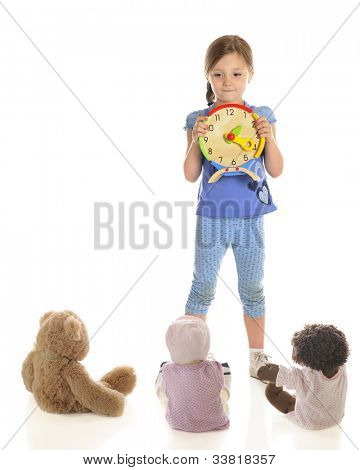 A attractive young elementary girl teaching her toys to tell time.  On a white background with plenty of space on the left for your text.
