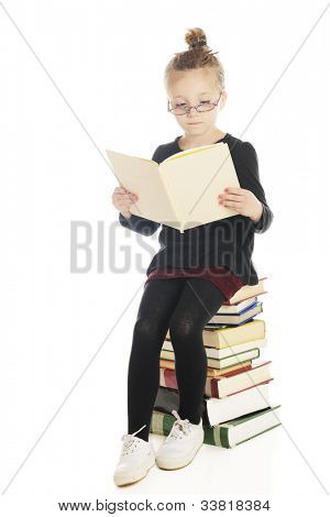 An adorable elementary reader sitting on a tall stack of books with low colorful glasses and her hair in a bun.  On a white background.