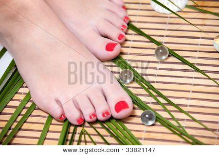 Beautiful feet leg with perfect spa pedicure on bamboo