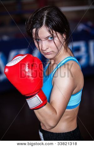 young and fit female fighter posing in combat poses