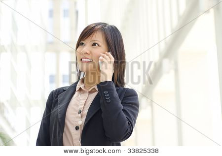 Asian Businesswoman walking on street passing by an office building.