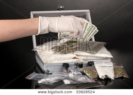 Cocaine and marijuana in a suitcase wiht hand holding a package of cocaine isolated on white