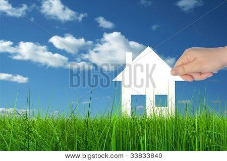 Concepto o documento conceptual Casa sostuvo en la mano por un hombre en un verano verde hierba sobre un azul sk