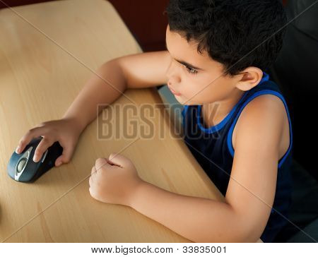 Small hispanic boy working on a computer or browsing the web at home photographed from above