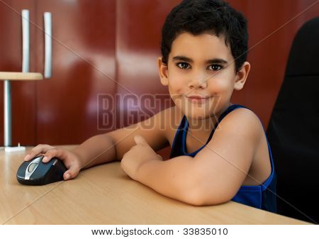 Cute small hispanic boy working on a computer at home and smiling