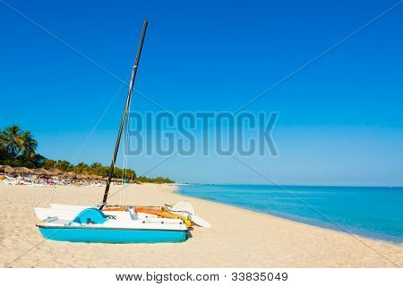 Sailing boats and thatched umbrellas on the  beach of Varadero in Cuba on a beautiful  summer day