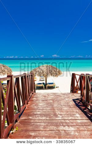Walkway leading from a resort to a tropical beach in Cuba on a beautiful summer day