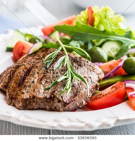 Grilled beef steak with salad and rosemary sprig