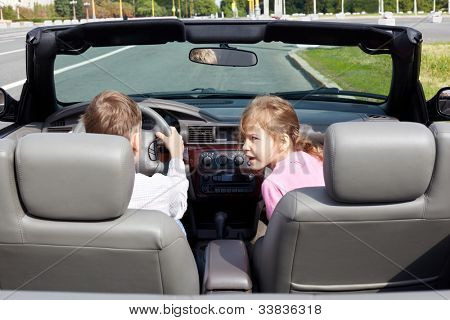Boy sits on driver seat in open top car and his sister sits half-turned back on passenger seat , back view.