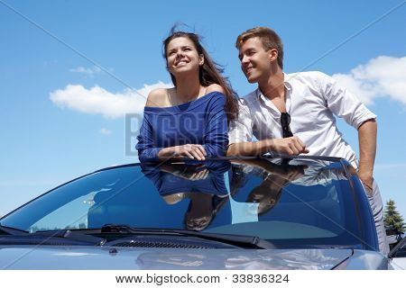 Young couple stands in cabriolet leaning their elbows on windshield, smiles and talks